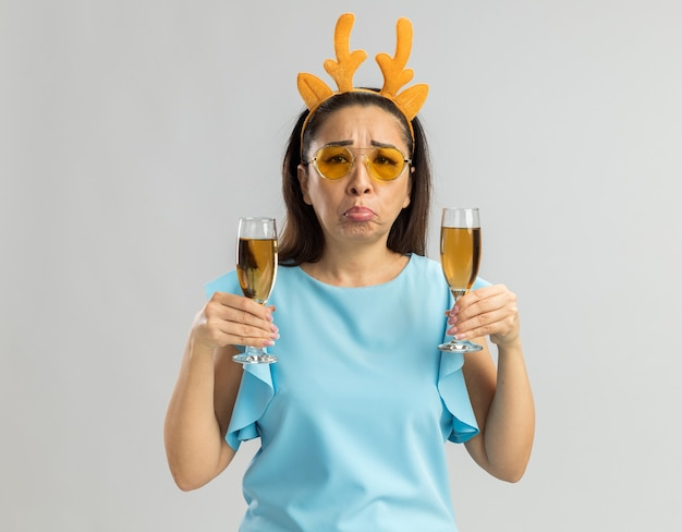 Verärgerte junge frau in der blauen spitze, die lustigen rand mit hirschhörnern und gelben gläsern hält, die zwei gläser champagner halten, die mit traurigem ausdruck spitzen lippen verfolgen