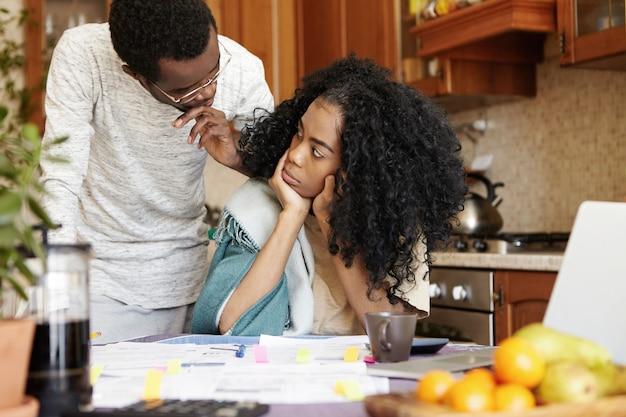 Verärgerte junge frau mit afro-haarschnitt, die ihren ehemann mit enttäuschung während des streits über schulden zu hause ansieht und am küchentisch mit vielen papieren und laptop sitzt. konzept für finanzielle probleme