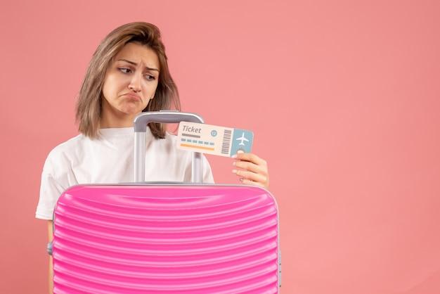 Verärgerte junge frau mit rosa koffer, die auf das ticket schaut
