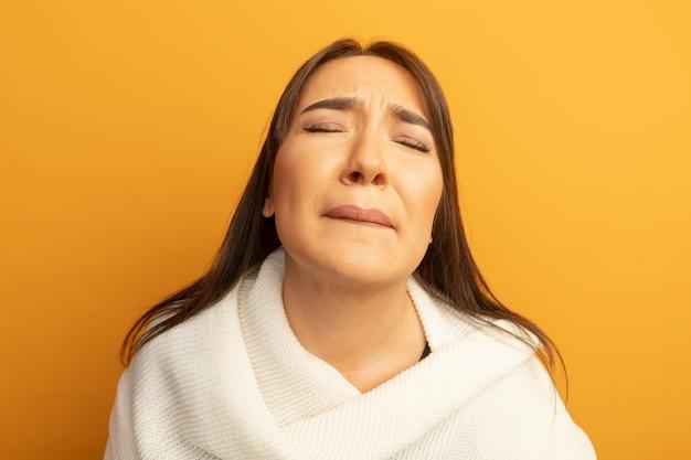 Verärgerte junge frau mit weißem schal mit geschlossenen augen mit traurigem ausdruck, der über orange wand steht