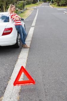 Verärgerte junge frau neben ihrem kaputten auto