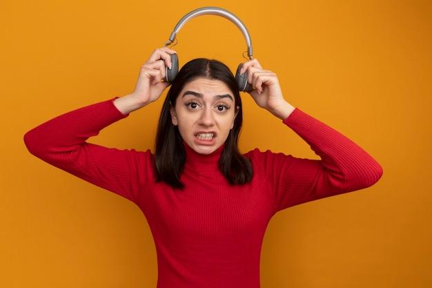 Verärgerte junge hübsche frau, die kopfhörer über dem kopf hält und nach vorne auf orangefarbene wand schaut?