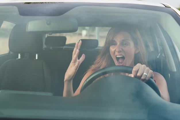 Verärgerte junge hübsche frau in ihrem auto beim fahren. verkehrssicherheitskonzept