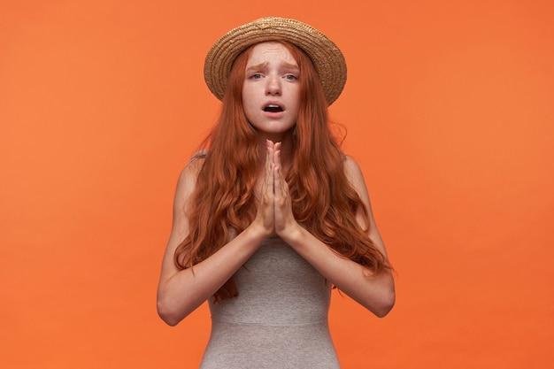 Verärgerte junge hübsche frau mit gewelltem rotem langem haar, das über orange hintergrund steht, handflächen zusammen in betender geste hält, auf besseres hofft, freizeitkleidung trägt