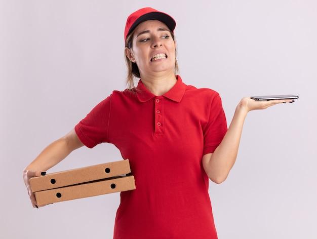 Verärgerte junge hübsche lieferfrau in uniform hält pizzaschachteln und betrachtet telefon isoliert auf weißer wand
