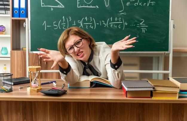 Verärgerte junge lehrerin mit brille sitzt am tisch mit schulwerkzeugen, die die hände im klassenzimmer ausbreiten