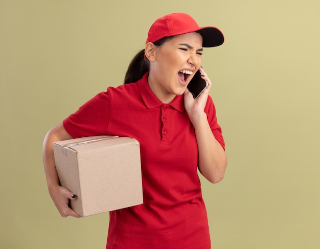 Verärgerte junge lieferfrau in der roten uniform und in der kappe, die den pappkarton hält, der schreit, während auf mobiltelefon steht, das über grüner wand steht