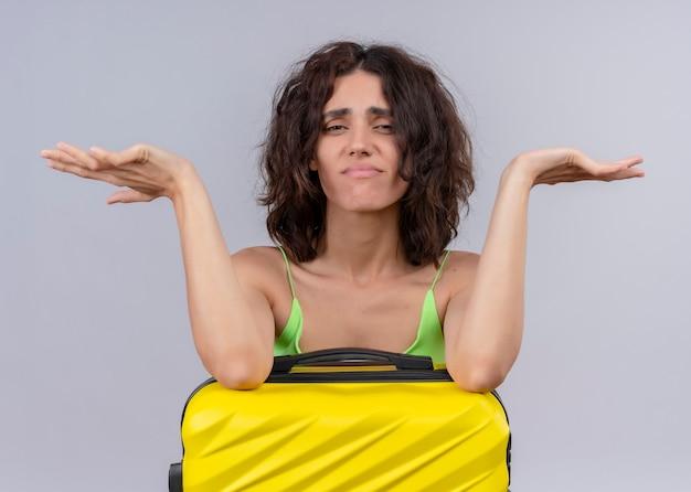 Verärgerte junge schöne reisende frau, die arme auf koffer setzt und leere hände auf isolierter weißer wand zeigt