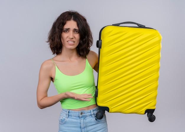 Verärgerte junge schöne reisende frau, die koffer hält und leere hand auf isolierter weißer wand zeigt