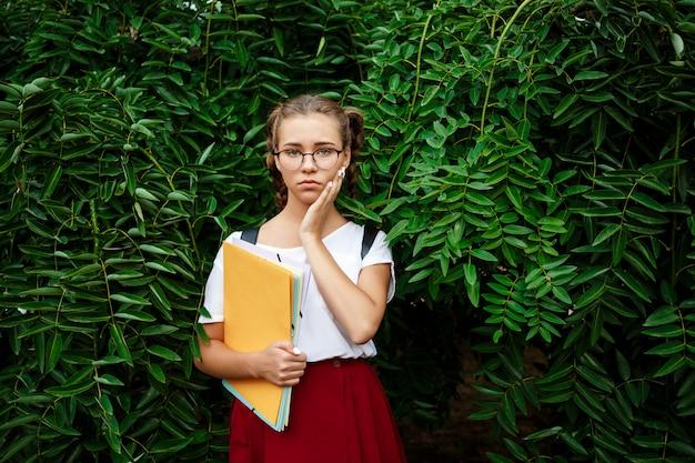 Verärgerte junge schöne studentin in gläsern, die ordner im freien halten.