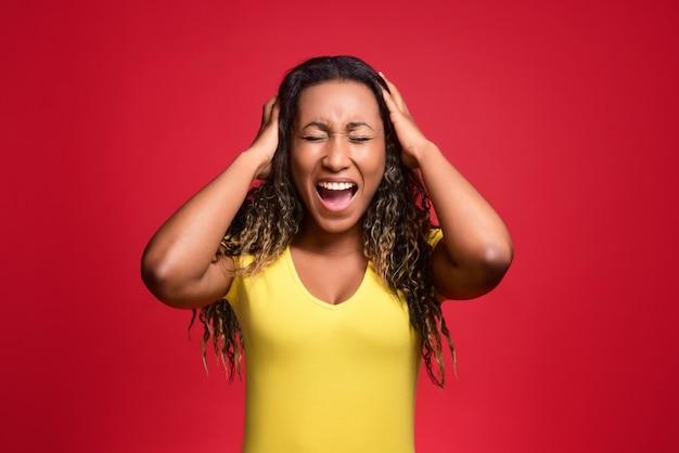 Verärgerte junge schwarze frau in stress, schreiend und ihren kopf umklammernd
