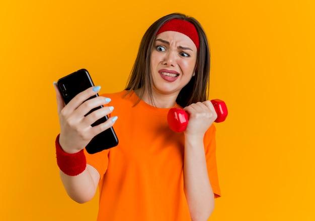 Verärgerte junge sportliche frau, die stirnband und armbänder hält, die hantel und handy halten und handy betrachten