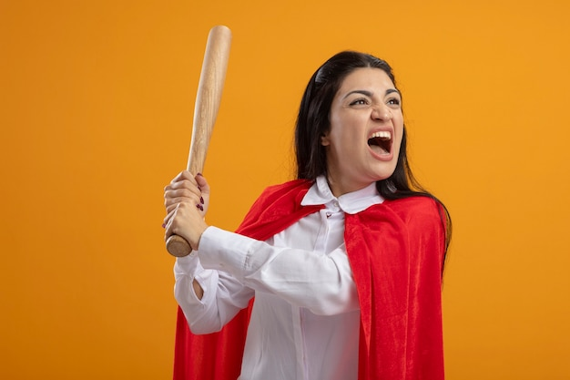 Verärgerte junge superfrau, die baseballschläger hält, der seite lokalisiert auf orange wand betrachtet