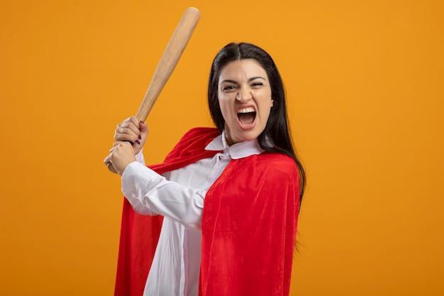 Verärgerte junge superfrau, die baseballschläger hält, der vorne auf orange wand lokalisiert betrachtet