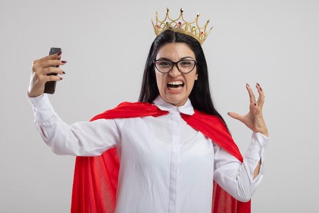 Verärgerte junge superfrau, die brille und krone hält handy hält hand in der luft, die front lokalisiert auf weißer wand hält