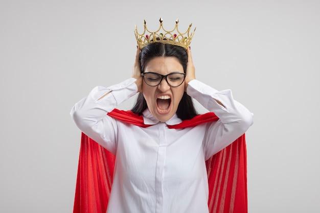 Verärgerte junge superfrau, die brille und krone trägt und hände auf ohren legt, die mit geschlossenen augen schreien, die auf weißer wand isoliert werden