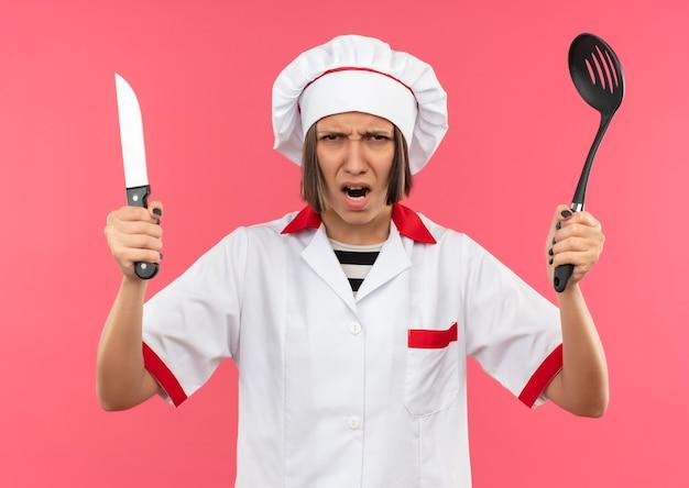 Verärgerte junge weibliche köchin in der kochuniform, die spatel und messer lokalisiert auf rosa hält