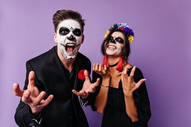 Verärgerte jungen und mädchen in totenkopfmasken posieren emotional und wollen ihre größe zeigen. porträt eines dunkelhaarigen mexikanischen paares.
