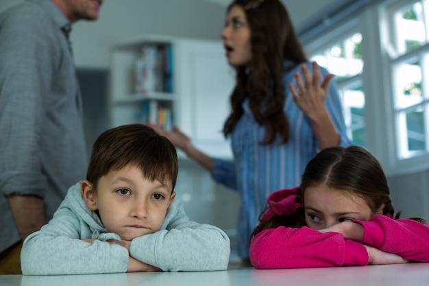 Verärgerte kinder sitzen, während paar miteinander streiten