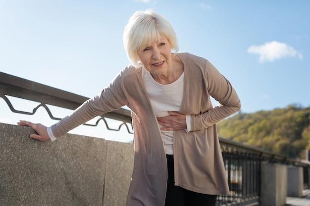 Verärgerte kranke dame mittleren alters, die negative gefühle ausdrückt, die nahe dem zaun stehen, während sie bauchschmerzen haben