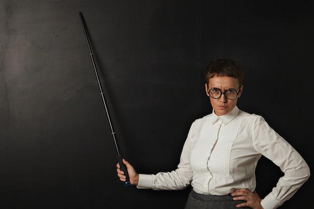 Verärgerte lehrerin und zeigt auf schwarzer kreidetafel hinter sich mit klappzeiger