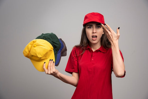 Verärgerte lieferfrau in der roten uniform, die bunte kappen hält.