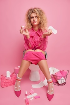 Verärgerte lockige junge frau hält damenbinde und baumwolltampon vergleicht zwei varianten der frauenhygiene trägt modisches outfit und bereitet sich auf formelle besprechungsposen auf der toilettenschüssel vor