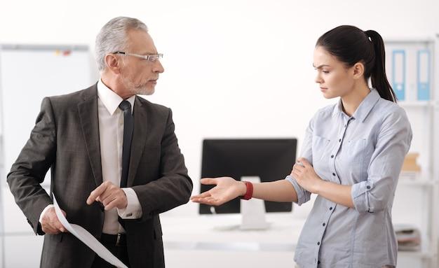 Verärgerte männliche person, die kostüm hält dokument in der rechten hand beim betrachten seines arbeiters trägt