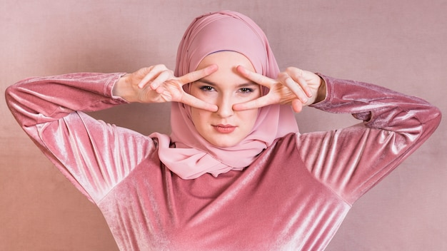 Verärgerte moslemische frau, die v-zeichen nahe ihren augen über farbiger oberfläche zeigt