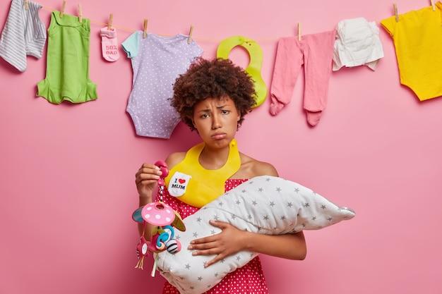 Verärgerte müde mutter posiert mit neugeborenen, hält mobiles spielzeug, lätzchen am hals, beschäftigt stillendes kind, braucht hilfe des ehemanns, spielt und füttert kleines kürzlich geborenes kind. postnatale depression, stimmungsstörung