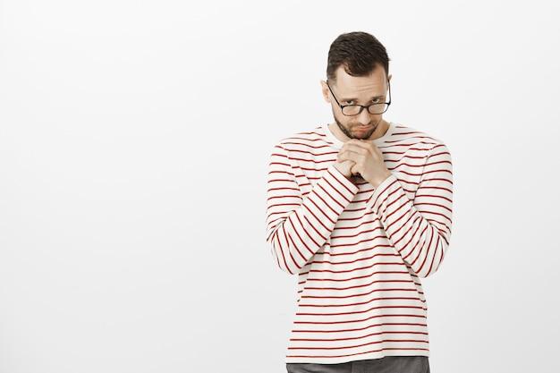 Verärgerte niedlichen mann in brille, hielt handflächen auf der brust und schaute mit traurigem ausdruck unter der stirn hervor
