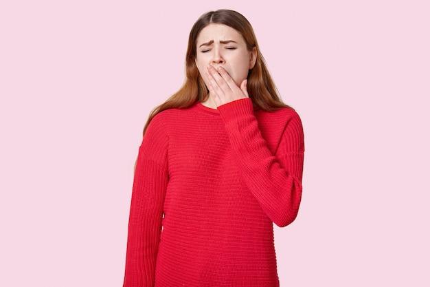 Verärgerte schläfrige frau gähnt und bedeckt den mund mit der handfläche