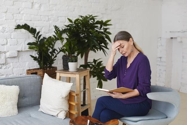 Verärgerte schöne 60-jährige frau, die auf grauem stuhl im wohnzimmer sitzt, stirn berührt und offenes heft auf ihrem schoß betrachtet, frustriert, weil sie wichtige besprechung vergaß