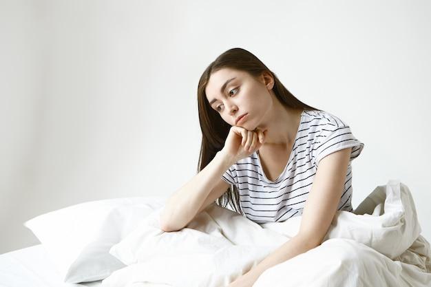 Verärgerte schöne junge frau mit langen braunen haaren, die auf dem bett sitzt, nachdenklich aussieht, nicht zur arbeit gehen will, sich krank und müde von ihrem langweiligen eintönigen leben fühlt