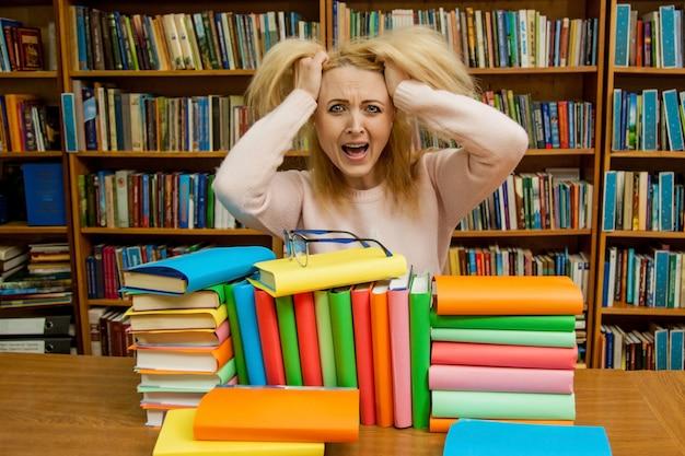 Verärgerte schreiende frau, kaukasisches mädchen mit dem langen haar, schreiend mit wut in der bibliothek