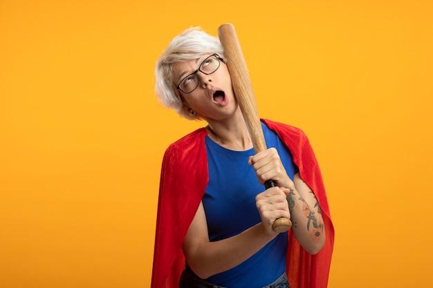 Verärgerte superfrau mit rotem umhang in optischer brille hält baseballschläger und schaut isoliert auf orange wand auf