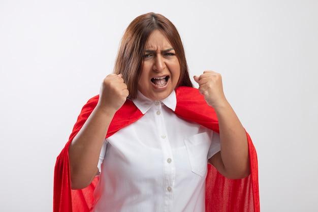 Verärgerte superheldenfrau mittleren alters, die kamera betrachtet, die ja geste lokalisiert auf weiß zeigt