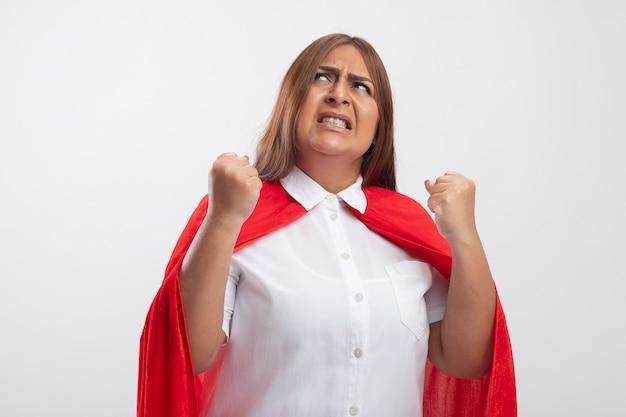Verärgerte superheldenfrau mittleren alters, die nach oben schaut und ja geste auf weiß isoliert zeigt