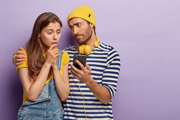 Verärgerte tausendjährige frau und mann benutzen digitale geräte, schauen traurig auf den bildschirm, schauen erbärmlichen film online, fühlen sich nervös
