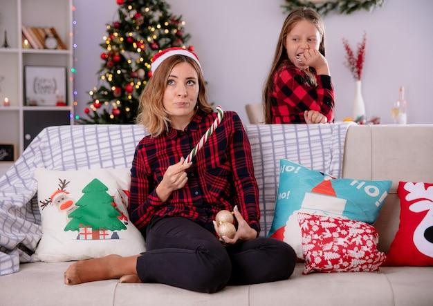 Verärgerte tochter isst einen teil der zuckerstange, die mutter mit weihnachtsmütze betrachtet, die einen teil der zerbrochenen zuckerstange und der glaskugelverzierungen hält, die auf der couchweihnachtszeit zu hause sitzen