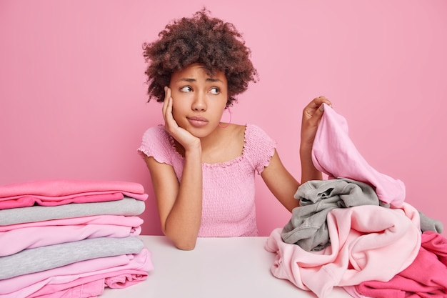 Verärgerte traurige afroamerikanische hausfrau pflückt kleidung vom stapel, faltet wäsche nach dem waschen hat müden unzufriedenheitsausdruck sitzt am tisch isoliert über pink