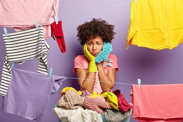 Verärgerte überarbeitete hausfrau hängt kleidung mit wäscheklammern an die wäscheleine