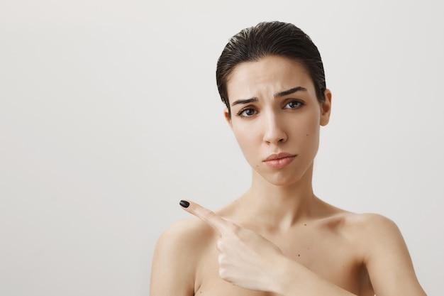 Verärgerte und enttäuschte frau, die nackt steht, traurig die stirn runzelt und nach links zeigt