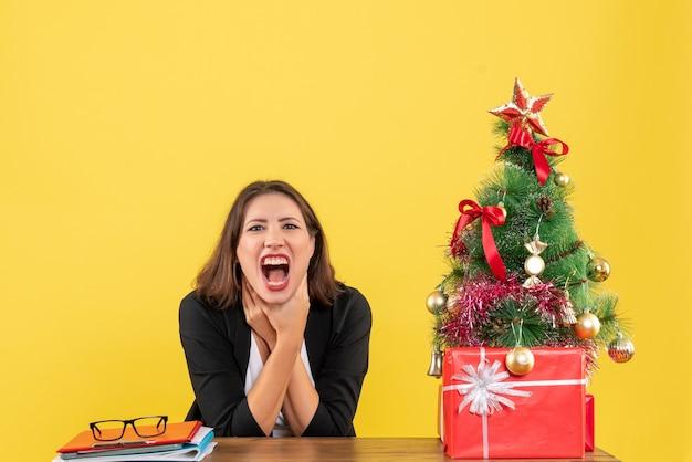 Verärgerte und nervöse junge frau, die an einem tisch nahe geschmücktem weihnachtsbaum im büro auf gelb sitzt
