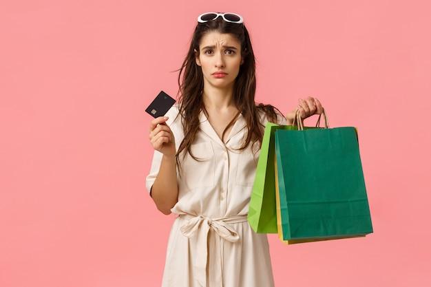 Verärgerte und verzweifelte junge brünette frau, die sich traurig fühlte, gab alles geld aus, sah unbehaglich und besorgt über kreditkarte aus, hielt einkaufstaschen, stand rosa hintergrund düster