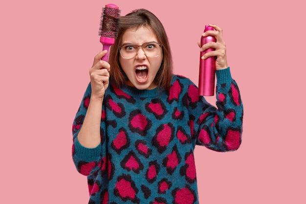 Verärgerte unzufriedene weibliche kämme haare, empört, macht frisur mit haarbürste und spray