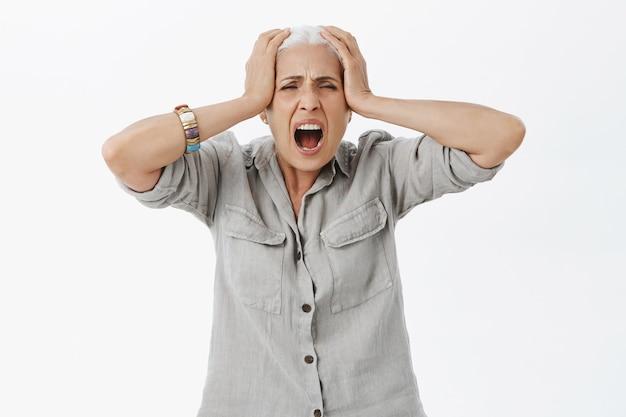 Verärgerte verzweifelte ältere frau, die schreit und hände auf dem kopf hält