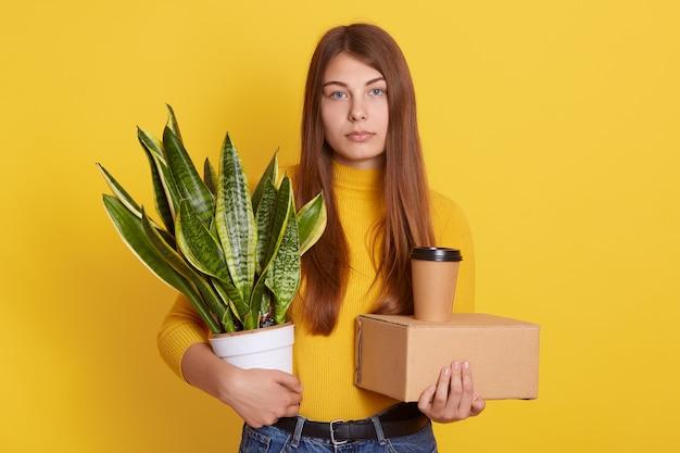 Verärgerte weibliche kleider lässige kleidung, die ihren stab und blumentopf mit bogenschnurhanf in den händen auf gelb hält