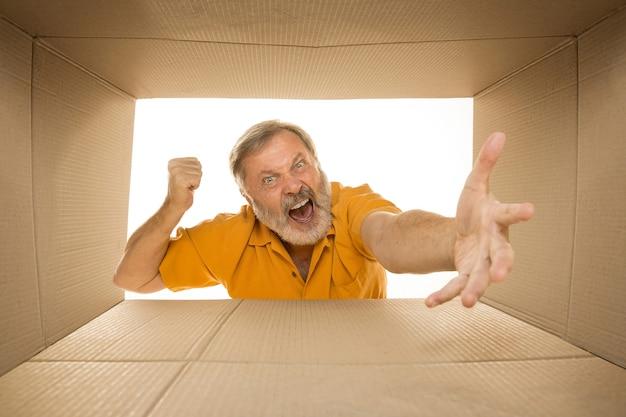 Verärgerter älterer mann, der das größte postpaket lokalisiert auf weiß öffnet. trauriges männliches model oben auf dem karton, der nach innen schaut.