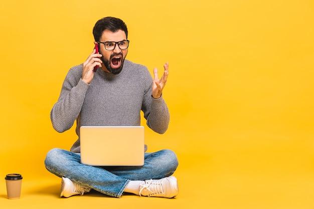Verärgerter aggressiver junger bärtiger mann, der mit laptop auf dem boden sitzt und am telefon spricht. isoliert über gelbem hintergrund.